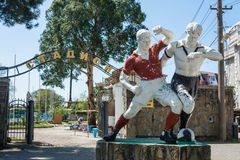 Old sculpture of two football players at the city stadium in Gag. Gagra, Abkhazia – April 15, 2016: Old sculpture of two football players at the city stadium Stock Photography