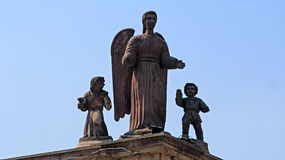 Old sculptures of a angel a boy and a girl. Outside of a church rest this three sculptures of one angel taking care of two children Stock Photos