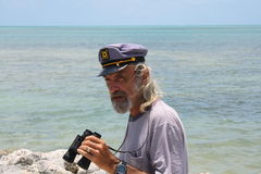Old sea Captain. By the sea with binoculars Stock Photos