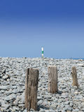 Old sea defense with beacon and pebbled beach in Aberystwyth Cer. Pebbled beach in Aberystwyth Ceredigion North Wales UK Stock Photography