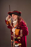 Old sea dog. Pirate's captain with musket, holding rope in hands, studio shot against gray background Stock Photos
