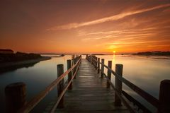 Old sea pier at sunrise on a calm lake Royalty Free Stock Photos