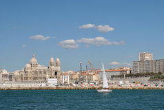 The old sea-port of Marseille, snowy sailing boat in the azure waters and Cathedral of Sainte-Marie-Majeure at back. Marseille, Provence, France - Sept. 10, 2010 Royalty Free Stock Photos
