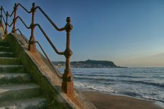 Old Seafront iron railings, View towards Scarborough. Weathered and Rusty railings and concrete steps royalty free stock image