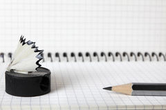 An old, second-hand, sharpener with a shavings and a simple pencil lie on the notebook in a box. Selective focus. Close-up. Stock Image