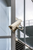 Old security camera on a glass wall Royalty Free Stock Photos