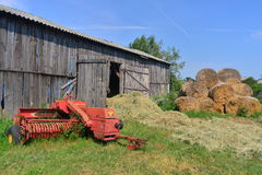 Old seeder. Old red seeder near an old barn and hay ballots in the village of Rodowo, northern Poland Stock Photo