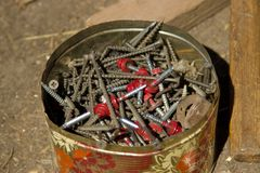 Old self-tapping screws, screwed in a tin box, hammer. Stock Photo