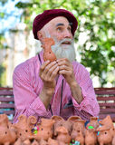 The    old seller clay toys -   and his handmade tin whistle Stock Photo