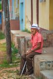 Poor Cuban people Old man sitting in street of Caribbean communism village with cigar, Cuba, America. An Old senior Cuban people man with a cigar and hat in royalty free stock image