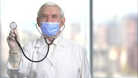 Old senior doctor holding stethoscope towards camera. Front view portrait of male grandpa, blurred city window background stock footage