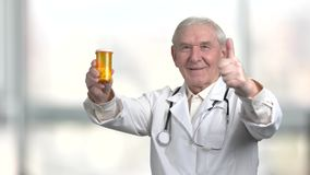 Old senior doctor recommend pills. Pointing at the can of pills and making thumb up in blurred windows background stock video footage
