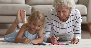Old grandma teach little granddaughter drawing with felt pen together