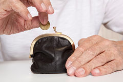 Old senior hands holding coin and small money pouch Royalty Free Stock Images