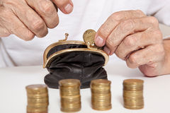 Old senior hands holding coin and small money pouch Stock Photos