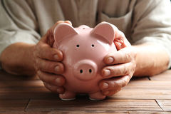 Old senior. Hands of old senior with piggybank on a wooden table Royalty Free Stock Photo