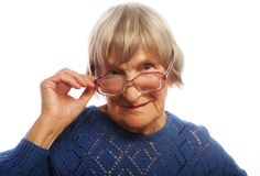Old senior lady looking through her eyeglasses. Isolated on white background Royalty Free Stock Photography