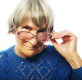 Old senior lady looking through her eyeglasses. Isolated on white background Royalty Free Stock Photo