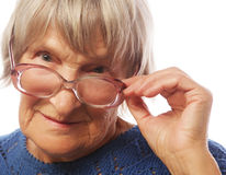 Old senior lady looking through her eyeglasses. Isolated on white background Stock Image