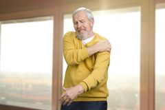 Old senior man with shoulder pain. Grandpa with shoulder inhury at home. Windows background stock photos