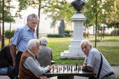 Old senior men playing chess in a park of Kalemegdan fortress, in Belgrade, Serbia. BELGRADE, SERBIA - JULY 11, 2018: . ..Picture of aged men playing chess in stock photography