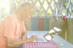 Old senior retired man working on a laptop computer in summer alcove royalty free stock images