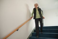 Senior woman walking down the stairs stock image