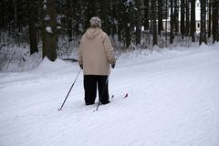 Of old senior woman with skis outside royalty free stock photo