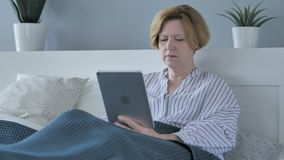 Old Senior Woman Using Tablet while Lying in Bed stock video