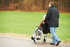 Old senior woman in wheelchair with careful son. Caregiver careful men walking and embracing disabled senior women grandmother at wheelchair in nature stock image