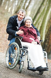 Old senior woman in wheelchair with careful son. Caregiver careful men walking and embracing disabled senior women grandmother at wheelchair in nature royalty free stock photography