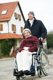 Old senior woman in wheelchair with careful son. Caregiver careful men walking and embracing disabled senior women grandmother at wheelchair in nature Royalty Free Stock Photo
