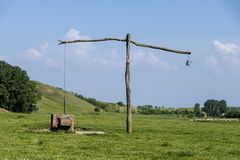 Old serbian sweep well and shadoof on the green meadow Stock Photography