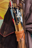 Old set of historic arrows with bright plumage in a leather quiver Stock Photo