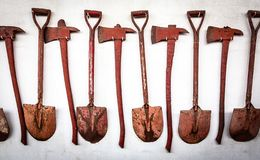 The old set of tools,shovel and ax is hanging on the old white wall. Background royalty free stock photos