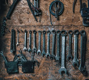 Old set of wrenches. A set of wrenches and working tools on a wall of plywood in a dirty garage Stock Photography