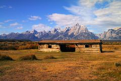 An old settlers cabin foreground the Tetons Royalty Free Stock Photos