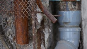 Old sewer in a house under repair. Plastic pipes for water in a broken wall