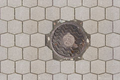 An old sewer manhole cover surrounded by pavement. Road street Stock Photography