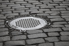 Old sewer manhole on dark cobblestone Stock Photography