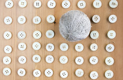 Old sewing buttons and ball of linen threads in the middle as pattern. Flat lay, top view Royalty Free Stock Image