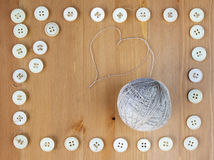 Old sewing buttons frame and ball of linen threads in the middle. Flat lay, top view. Copy space Royalty Free Stock Image
