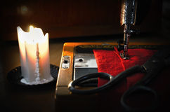 Old sewing machine, fabric and rusty scissors at the light candl Stock Photos