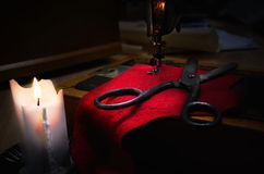 Old sewing machine, fabric and rusty scissors at the light candl Royalty Free Stock Image