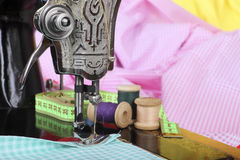 On the old sewing machine lie wooden retro coils with threads, a thimble, a measuring tape and a piece of cotton fabric. Close-up. Stock Image