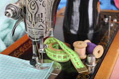 On the old sewing machine lie wooden retro coils with threads; a thimble, a measuring tape and a piece of cotton fabric. Focus on Royalty Free Stock Photos