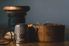 Old sewing machine needle with black thread, on a old grungy work table. Tailor`s work table. textile or fine cloth making. indust royalty free stock image