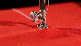 Old sewing machine on red cloth, close up, slow. Old silver sewing machine with white thread on red cloth, close up, slow motion stock video