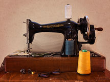 Old sewing machine with scissors and glasses. Stock Image