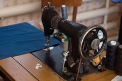 The old sewing machine is sewn blue cloth in the home workshop.  Stock Photo